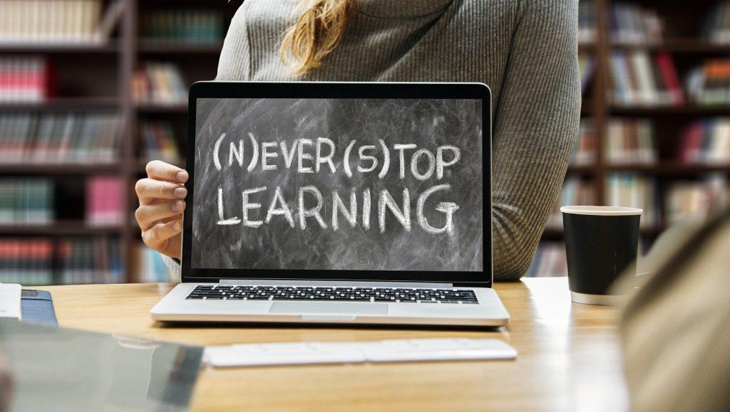 Laptop op tafel met op het beeldscherm een schoolbord waarop de tekst (n)ever (st)op learning staat.