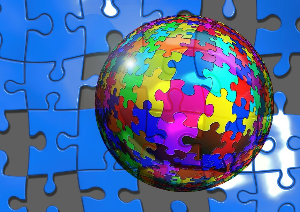 Bal met daarop gekleurde puzzelstukjes en op de achtergrond blauwe of ontbrekende puzzelstukjes